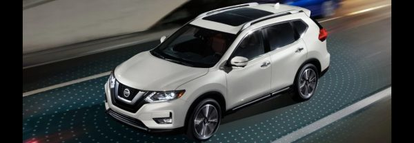 White 2019 Nissan Rogue driving with Nissan Intelligent Mobility lights around it