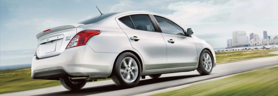 Silver 2019 Nissan Versa Sedan driving on the highway towards a city.