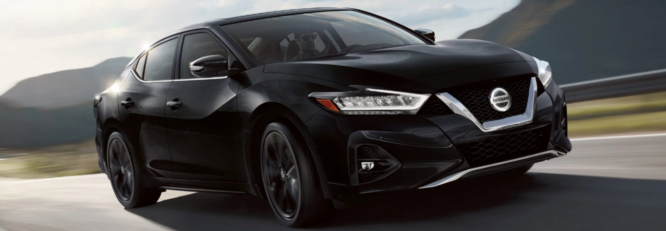2019 Nissan Maxima in black driving on a mountain highway