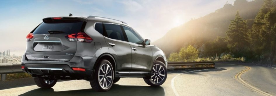2019 Nissan Rogue in silver parked along a scenic highway.